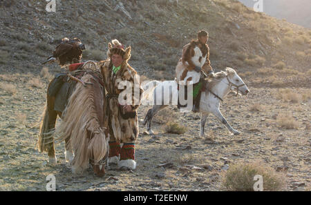 bayan Ulgii, Mongolia, 3rd October 2015: kazakh eagle hunter with his eagle and a horse - Stock Photo