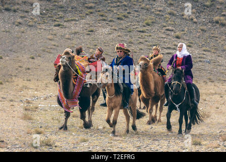 bayan Ulgii, Mongolia, 3rd October 2015: mongolian nomads traveling on horses and camels in a landscape of Western Mongolia - Stock Photo
