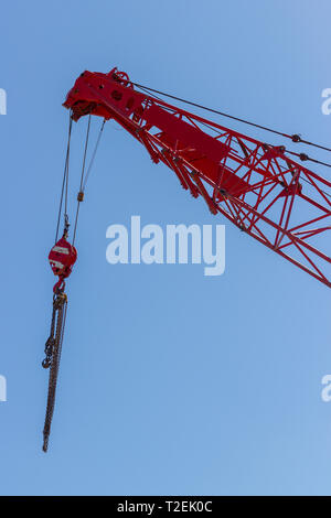 Red crane top with hook and lifting chains against clear blue sky - Stock Photo