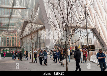 Tourists in the plaza of Hudson Yards pass 'The Shed' arts space as workers prepare it for its opening, seen on Saturday, March 30, 2019 . (© Richard B. Levine) - Stock Photo