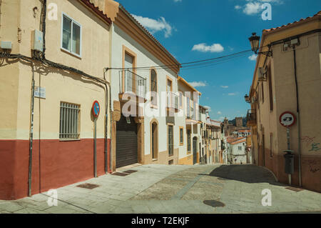 Alley in slope with traffic signs and old buildings, in a sunny day at Caceres. A charming town with a fully preserved old city center in Spain. - Stock Photo