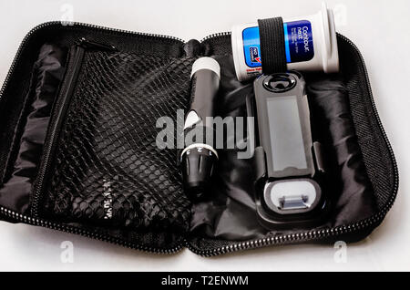 A Contour Next blood glucose monitoring kit is pictured on white, along with the meter, glucose test strips, and lancet device, March 30, 2019. - Stock Photo