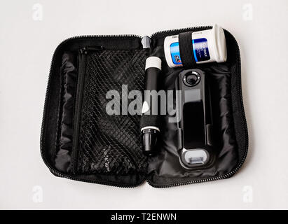 A Contour Next blood glucose monitoring kit is pictured on white, along with the meter, glucose test strips, and lancet device,​ March 30, 2019. - Stock Photo