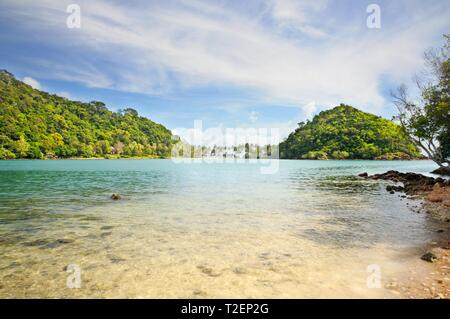 Crystal clear tropical sea with island covered with rainforest on horizon at the Koh Chang island, Thailand. - Stock Photo