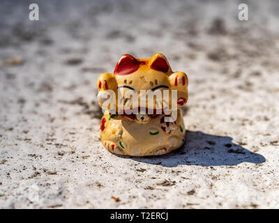 A small weathered lucky cat figurine sits on a residential wall, where it seems to have been sitting for a long time. - Stock Photo