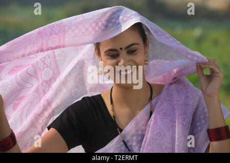Portrait of a woman traditionally dressed with her head covered by saree. - Stock Photo