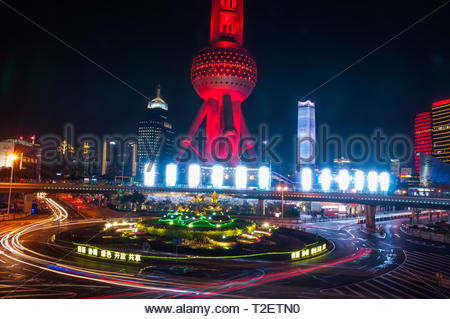 The Oriental Pearl Tower seen at night from the Lujiazui skywalk with the Mingzhu Roundabout in front. - Stock Photo