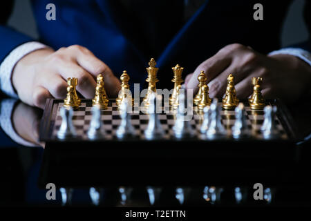 Cropped image of businessman in suit thinking over movement while sitting at glass table and playing chess