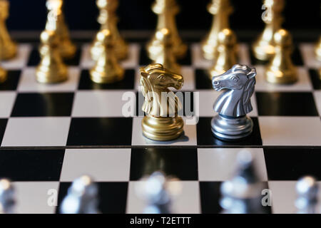 Closeup shot of chess knights placed on chessboard in front of each other representing competition in business world - Stock Photo