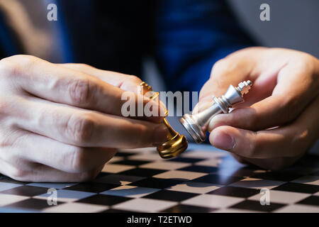 Closeup shot of hands of unrecognizable businessman holding two kings and making them fight over chess board - Stock Photo