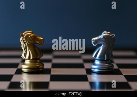 Closeup golden and silver horse knights places against each other on chessboard against gray background - Stock Photo