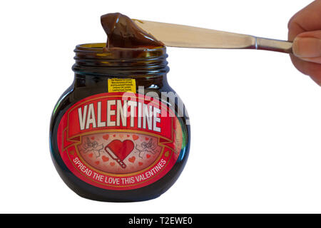 Hand holding knife getting Marmite out of jar set on white background - Special edition jar of Valentine Marmite by Unilever - Stock Photo