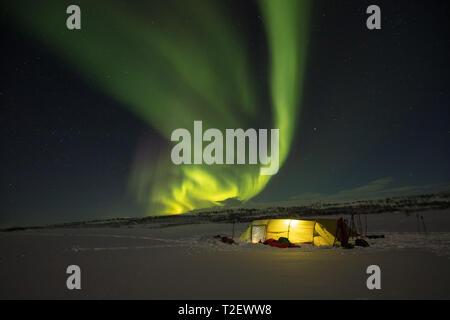 Aurora borealis over a winter ski touring tent. Finnmarksvidda Plateau. Finnmark, Arctic Norway. - Stock Photo