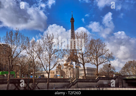 Panoramic view of the Eiffel Tower from the point of view of a boat cruising along the Seine river against a deep blue sky. Paris, France, Europe - Stock Photo