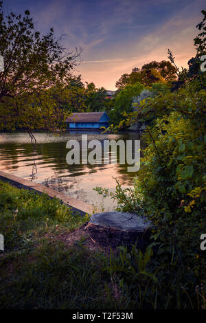 Beautiful evening scene in Herastrau Park in Bucharest Romania with a blue picturesque house in the background over the lake and a tree trunk - Stock Photo