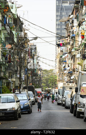 Daily traffic and city life on the narrow streets of Yangon during sunset. - Stock Photo