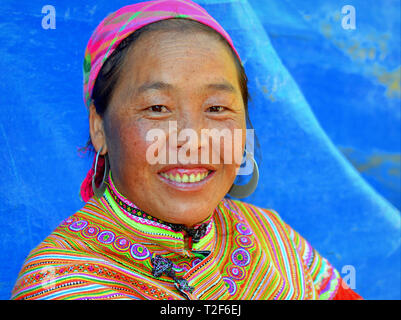Middle-aged Vietnamese Flower H'mong woman wears a colorful embroidered traditional Flower H'mong costume with large tribal silver earrings. - Stock Photo