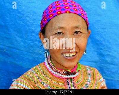 Middle-aged Vietnamese Flower H'mong woman wears a colorful embroidered traditional Flower H'mong costume and smiles for the camera. - Stock Photo