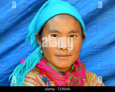 Young Vietnamese Flower H'mong woman wears a colorful embroidered traditional Flower H'mong costume and poses for the camera. - Stock Photo