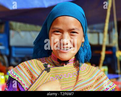 Young Vietnamese Flower H'mong woman wearsa colourful traditional Flower H'mong attire and a blue headscarf and smiles for the camera. - Stock Photo