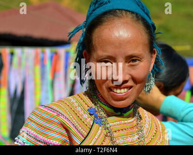 Mature Vietnamese Flower H'mong woman wears a colourful traditional Flower H'mong attire and smiles for the camera. - Stock Photo