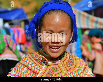 Young Vietnamese ethnic minority Flower H'mong woman wears a colourful traditional Flower H'mong outfit and smiles for the camera. - Stock Photo