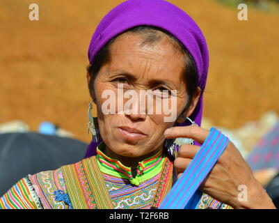 Middle-aged Vietnamese Flower H'mong saleswoman wears a colourful traditional Flower H'mong dress and a blue headscarf. - Stock Photo