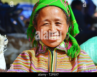Middle-aged Vietnamese Flower H'mong woman wears a colourful traditional Flower H'mong dress, a green headscarf and tribal silver earrings. - Stock Photo