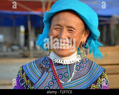 Elderly Vietnamese Blue H'mong hill-tribe woman with three gold teeth wears traditional H'mong embroidery in blue and smiles for the camera. - Stock Photo