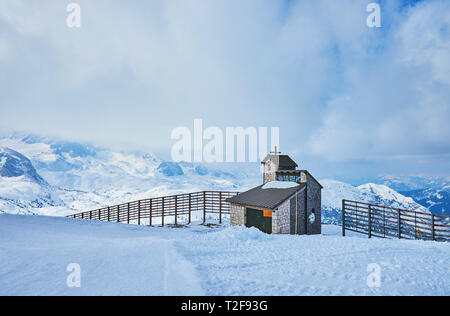 The small mountain chapel (Bergkapelle) on the edge of the snowy slope of Dachstein-Krippenstein mount with Alps, covered in  heavy clouds on the back - Stock Photo