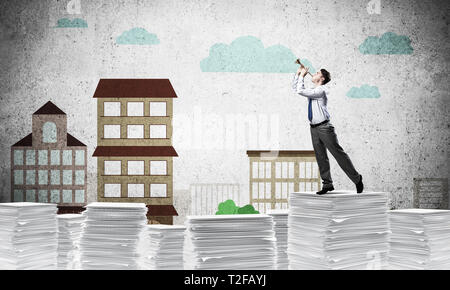 Businessman playing fife while standing on pile of documents with drawn cityscape on background. Mixed media. - Stock Photo