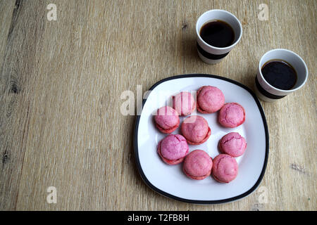 Coffee break with two cups of coffee and pink french macarons with raspberry filling - Stock Photo