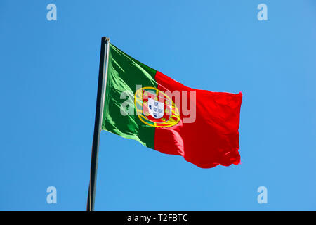 National Flag of Portugal blowing in the wind on flag pole with blue sky background. Portugal - Stock Photo