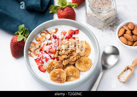 Smoothy bowl with banana, strawberry, granola, nuts on white table. Closeup view. Concept of healthy vegetarian diet, weight loss, balanced diet - Stock Photo