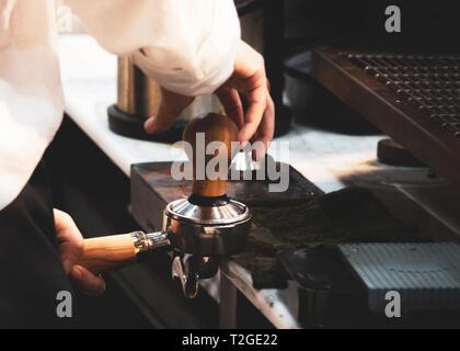 Barista working in a coffee shop, Close up of barista presses ground coffee using tamper, Barista Make Coffee Portafilter Concept - Stock Photo