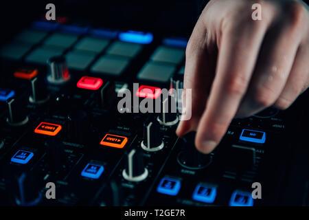 Dj hands adjusting controls on a mixer - Stock Photo