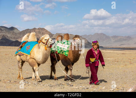 bayan Ulgii, Mongolia, 4th October 2015: nomad man with his camel in a landscape of Altai Mountains - Stock Photo