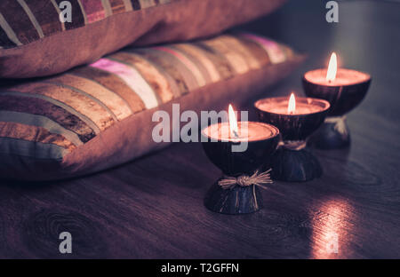 Burning spa aroma candles in coconut shell and  burgundy pillows with pattern, cozy home interior background - Stock Photo