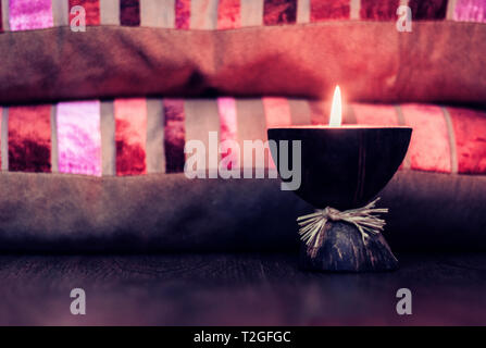 Burning spa aroma candle in coconut shell and  burgundy pillows with pattern, cozy home interior background - Stock Photo