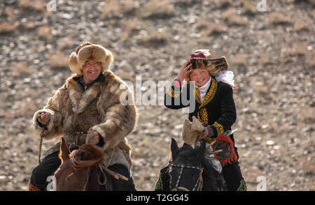 bayan Ulgii, Mongolia, 4th October 2015: kazakh eagle hunter  with his daughter, eagle huntress Aisholpan, traveling on their horses - Stock Photo