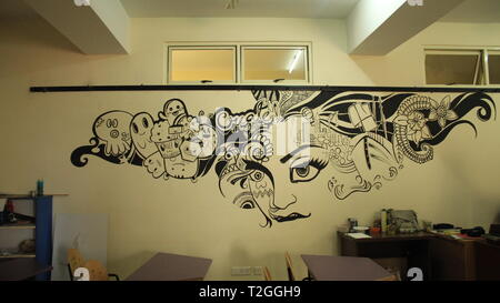 Art painting or drawing of a woman with wide hair indicating the world and things in black in art classroom. Art on Wall in Art Classroom in School. - Stock Photo