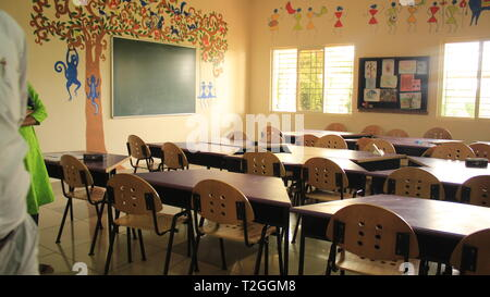 Art Classroom with Tables and Chairs with Art and designs on wall in School - Stock Photo