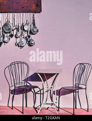 A table and two chairs outdoor with shadows . Kitchen pots and pans hanging in the background. Stock Image - Stock Photo
