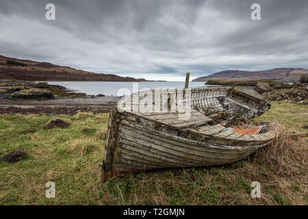 An old, abandoned and weathered fishing boat lying in some grass near a bay on the Isle of Mull, Hebrides, Scotland, UK - Stock Photo