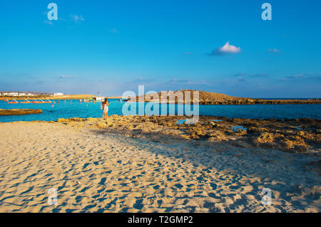 One Caucasian girl in a white dress standing, looking at the solitary breathtaking Nissi beach in Agia Napa, Cyprus. Yellow sand and reefs against blu - Stock Photo
