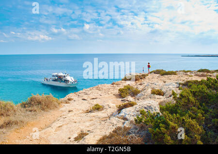 Two tiny figures of girls standing on the edge of a cliff. One white tourist ship in a bay near Cape Greco, Cyprus. Rock coastline near deep green tra - Stock Photo