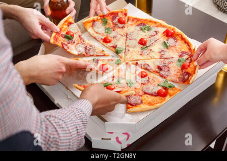 Lunch time. Friends eating delicious pizza, having home party, closeup - Stock Photo