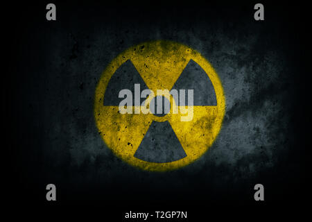 Radioactive (atomic nuclear ionizing radiation) danger warning yellow symbol shape painted on massive concrete cement wall grungy texture dark backgro - Stock Photo