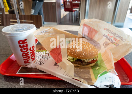 A whopper meal purchased at a Burger King fast food restaurant. A whopper burger and a cup of soda are seen on a tray on a table. - Stock Photo