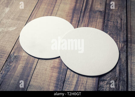 Photo of two blank beer coasters on wooden background. - Stock Photo